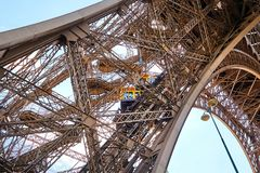 Yellow diagonal elevator inside the metal support of the Eiffel royalty free stock photo
