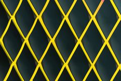 Yellow diamond-shaped lattice against a dark background royalty free stock image