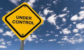 Under control. Yellow diamond shaped roadside sign with text 'under control' in black uppercase letters, background of blue sky and clouds Royalty Free Stock Photo
