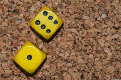 Yellow dices one six. On cork royalty free stock images