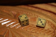 Yellow dices on a wooden board Stock Image