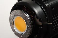 Yellow diffusing filter part of studio illuminator. Close-up - side view - a yellow diffusing filter part of the studio illuminator on a white background. Studio stock photos