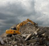 Yellow digger. Digger at work on a pile of rubble under a darkening sky Stock Photography