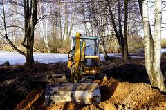 Yellow digger on the dam of pond, February royalty free stock photo