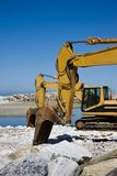 Yellow diggers on the seashore Stock Images