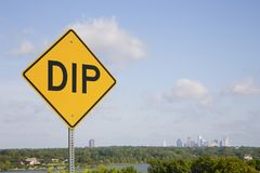 Yellow Dip Sign Against Blue Sky With City Skyline. A yellow, diamond shaped, DIP sign with black letters against a blue sky with a city skyline and room for Stock Photography