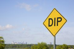 Yellow Dip Sign Against Blue Sky With City Skyline. A yellow, diamond shaped, DIP sign with black letters against a blue sky with a city skyline and room for Royalty Free Stock Photography