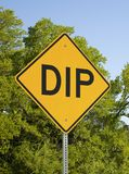 Yellow Dip Sign Against Blue Sky And Green Trees stock photos