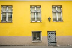 Yellow dirty wall of a dilapidated house on a cobbled street of the old city of Riga. stock image