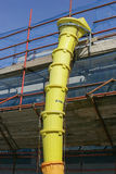 Yellow discharge chute construction debris. Scaffolding with slide for debris and rubble Royalty Free Stock Photography
