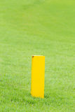 The yellow distance marker pole to inform range of golfing in gr Stock Image