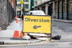 Yellow diversion road sign in a UK city street.  stock photos