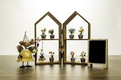 Yellow doll stand near the house frame with flower and blank black board Royalty Free Stock Image