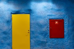 Yellow door on blue wall and red fire shield. stock photos