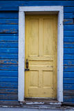A yellow door inset in a blue wood board wall Royalty Free Stock Photography