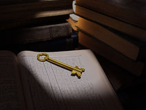 Yellow door key on the open book on the background of a stack of old books. Yellow door key in a beam of light on a page with a table on background stack of old royalty free stock images