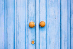 Yellow door knob on the blue wooden door. Mediterranean style stock photos