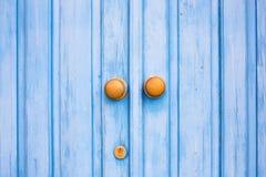 Yellow door knob on the blue wooden door. Stock Photos