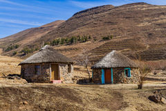 Yellow Door, Red Door. Traditional Basotho stone huts with colorful doorways, thatched roofs, and mountains in the background on a sunny winter day in rural Stock Image