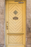 Yellow door at Stone House. Old yellow wooden door with a small window and welcome sign at Stone House Royalty Free Stock Images