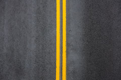 Yellow double solid line on asphalt Royalty Free Stock Photos