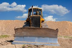Yellow dozer on a dirt terrain with blue sky. With clouds in the background royalty free stock images
