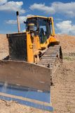 Yellow dozer on a dirt terrain with blue sky. With clouds in the background royalty free stock photography