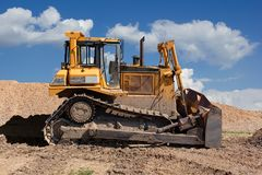 Yellow dozer on a dirt terrain with blue sky. With clouds in the background stock photography