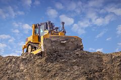 Yellow dozer pushes a pile of sand. Bulldozer working working on sand dune royalty free stock image