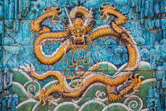 Yellow dragon with raised forepaws on the wall Stock Photos