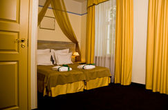 Yellow Drapery. A luxurious bedroom in a hotel with yellow furniture and drapery Royalty Free Stock Image