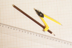 Yellow Drawing compass with black pencil and ruler on graph Royalty Free Stock Images