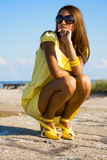 Yellow dress. Swarthy young girl poses on the beach Stock Photo