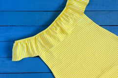 Yellow dress on blue wooden background. Womens clothing. Striped. Pattern Stock Images