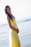 Yellow dress brunette beach Stock Image