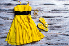 Yellow dress and flip flops. Casual dress, footwear and bracelets. Lady's bright summer apparel. Get ready for upcoming season royalty free stock photos