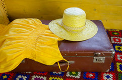 Yellow dress and straw hat lying on old suitcase Stock Images