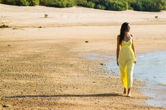 Yellow dress stroll on beach Royalty Free Stock Photos