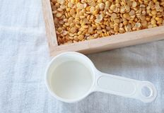 Yellow Dried Soybeans with Empty Measuring Spoon. Cuisine and Food, Top View of Empty Measuring Spoon with Dried Soybeans or Edamame Seeds in A Wooden Tray stock photos