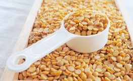 Yellow Dried Soybeans in A Measuring Spoon. Cuisine and Food, A Measuring Spoon Full of Dried Soybeans or Edamame Seeds in A Wooden Tray stock photography