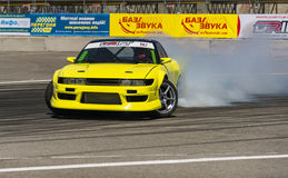 Yellow drift car brand Nissan overcome turn track Stock Photos
