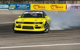 Yellow drift car brand Nissan overcome turn track Stock Photos