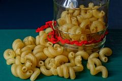 Yellow dry pasta and a glass jar. A bunch of fine dry yellow pasta on a green table and a glass jar Stock Photos