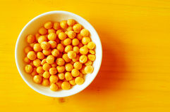 Yellow dry peas. Solid yellow dry peas in a white bowl on a yellow table closeup. Top view Royalty Free Stock Photos