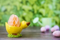 Yellow duck egg cup with honeycomb, against green background royalty free stock photo