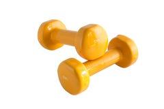 Yellow dumbbells 3. Two yellow shine dumbbells, isolated on white background Royalty Free Stock Image