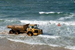 Free Yellow Dump Truck Drives Along The Sea Beach Near The Sign Swimming Is Prohibited In Israel Royalty Free Stock Image - 206788326
