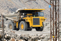 Yellow dump truck. Driving on a road in a stone quarry stock photography