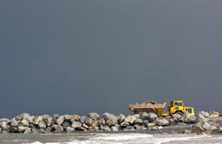 Yellow dumper truck building coastal defence works Royalty Free Stock Photo