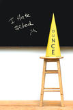 Yellow dunce hat on stool Royalty Free Stock Image